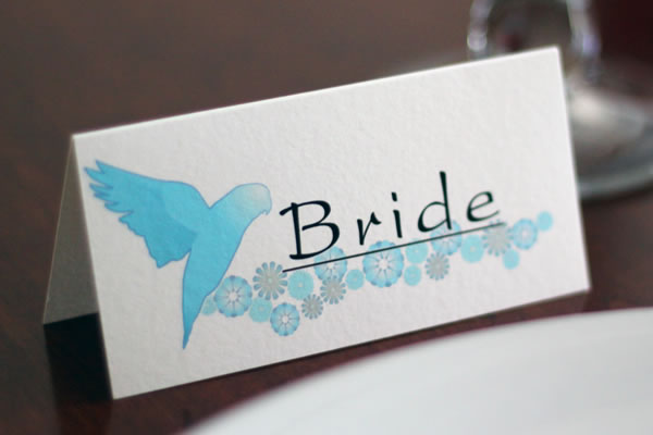 Bespoke wedding stationery and invitation range featuring pairs of lovebirds flying over a floral backdrop